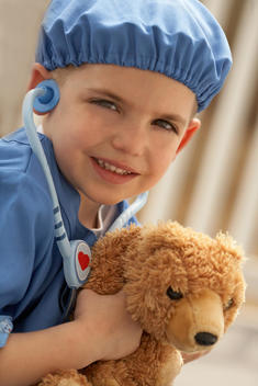 Young Boy In Doctor Suit Holding Stuffed Bear And Stethoscope