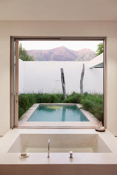 Modern bathroom overlooking swimming pool and mountains