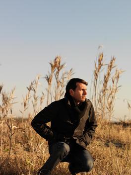 Man Sitting In Tall Grass