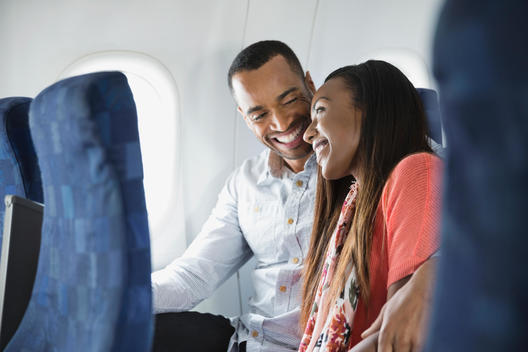Smiling couple snuggling in airplane