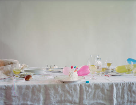 The Dog And The Wolf Series; Wrinkled White Tablecloth, White Dishes, Glassware, Half-Eaten Birthday Cake With Candles, Pink, Yellow, And Blue Balloons, Wine Glasses