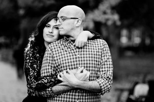 Black and White image of loving engaged couple with woman in lace and bald man in glasses embracing in city park