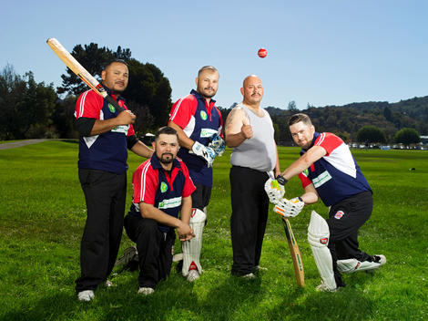 Members of a cricket team pose with their bats, balls, and gear on the field