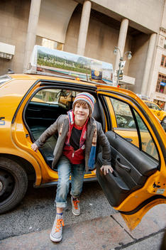 boy getting out of taxi