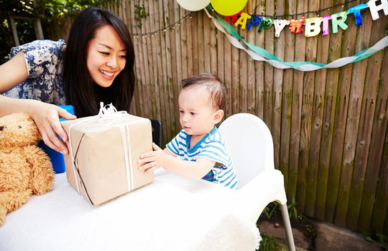 Mother handing birthday gift to baby boy