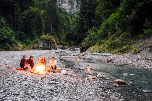 group of people of all ages sitting around campfire at rocky creek in mountainous landscape