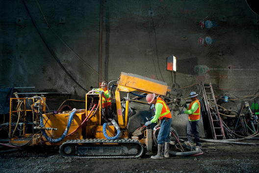 Construction workers are inspecting a piece of heavy machinery inside Caldecott Tunnel near Oakland