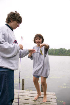 Mother And Daughter Fishing Together Off A Dock, Blue Lake, Minnesota, Usa.