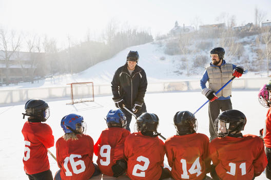 Coaches and ice hockey team on rink