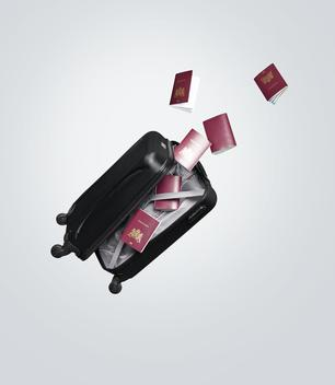 A suitcase flying open with passports flying out.