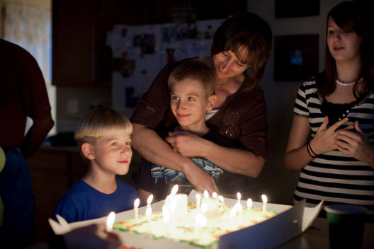 A Family Celebrates A Birthday Party In The Kitchen Of Their Suburban Home.