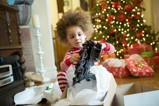 Mixed race boy opening Christmas presents