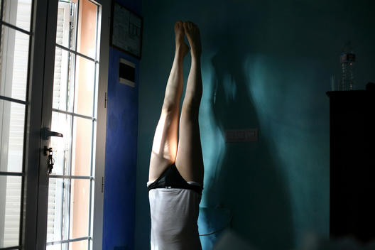 Woman Performing Handstand In Room