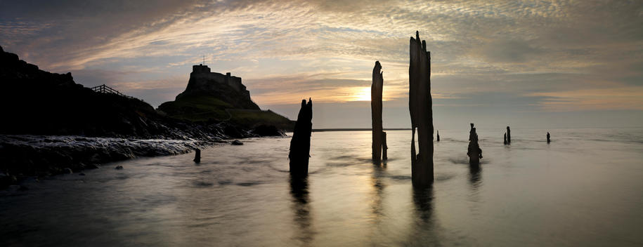 Panoramic View Of The Coastline With Lindisfarne Castle In The Background.