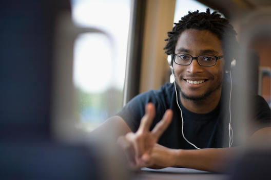 African man listening to headphones and gesturing peace sign