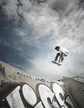 Man Jumping Over The Lip Of A Skateboard Ramp With Graffiti, Ontario, Canada.