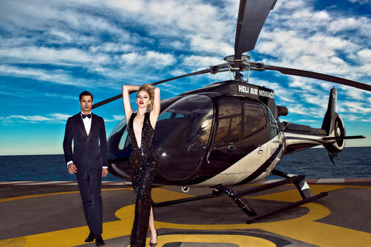 A couple look very chic walking in front of a helicopter arriving in Europe.