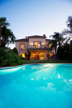 Luxury swimming pool and villa at dusk