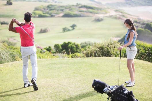 Couple teeing off on golf course