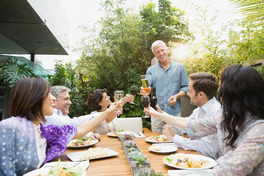 Friends toasting drinks at outdoor dinner party