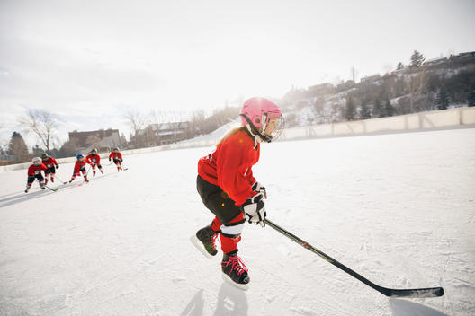 Girl playing ice hockey on rink