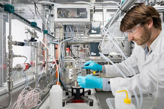 Male scientist, doing research on a innovative technology for mixing chemicals, at a hightech startup company