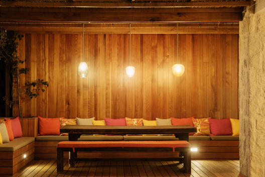 Pendant lights illuminated over patio bench with cushions
