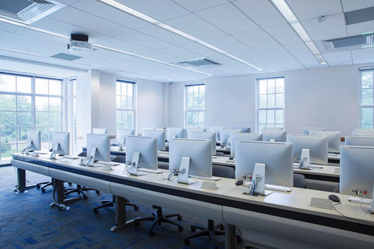 Bright, modern college classroom with rows of computers of desktops.