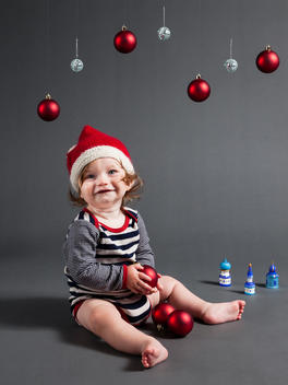 Smiling nine month old baby boy playing with baubles and wearing a Christmas hat.