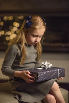 Non-specific holiday portrait of a young girl holding a gift on her lap in front of a fireplace onto which holiday lights are reflected.