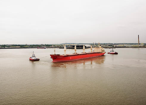Bulk cargo ship in the Thames River with tugs positioning the ship for berthing at Tilbury docks.
