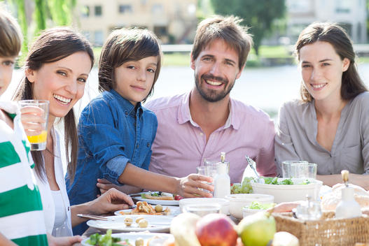 Family eating together outdoors, portrait