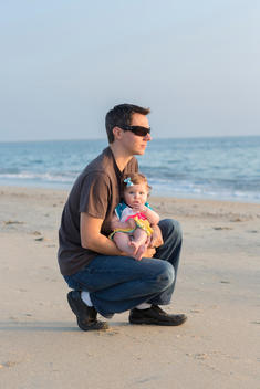 Father holding baby on the beach; baby looking at camera, man looking into distance.