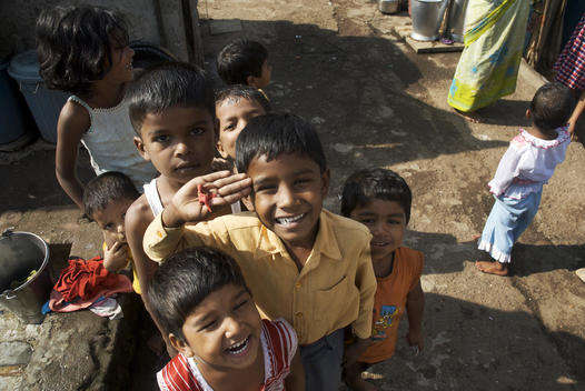 Children gathered together smiling, one saluting