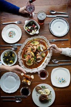 Aerial view of a table of people sharing a main dish and wine.