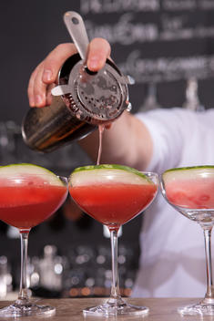 A bartender pours a drink into a martini glass containing a watermelon slice.