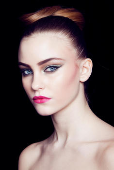 beauty image of model in studio, fair skin, brown hair in an updo with strong eyes and a pink lip