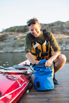 Portrait of happy man searching something in bag by kayak on pier