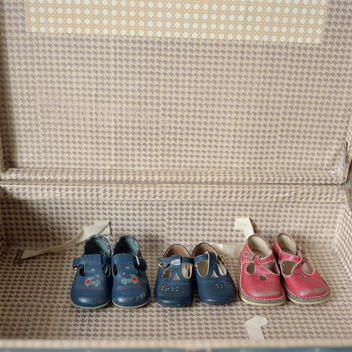 Children\'s Shoes Lined Up In A Row Inside A Suitcase