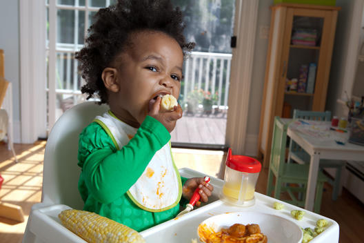 Action Shot Of Baby Eating Corn In A Highchair