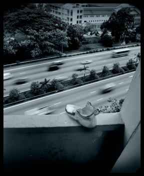 A Monopoly Icon Shoe On The Edge Of A Building Wall Looking Down On Heavy Traffic Highway.