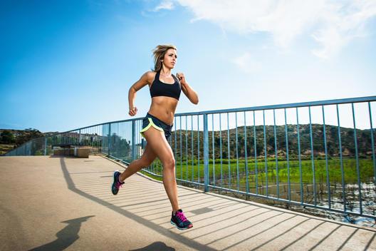 Athletic woman running on bridge
