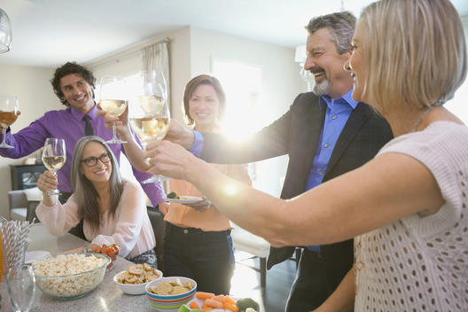Cheerful family and friends toasting drinks at party