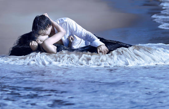 A young couple kissing on a beach with waves washing over them