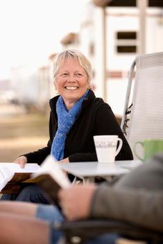 Senior Caucasian woman reading outside motor home