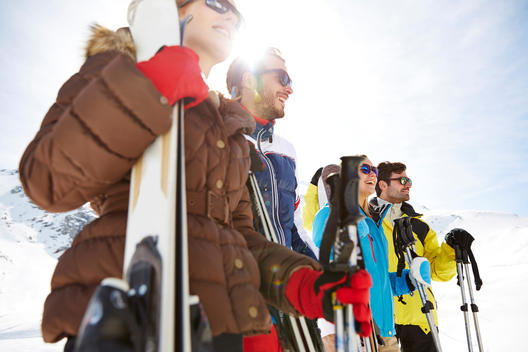 Friends standing with skis on mountain top