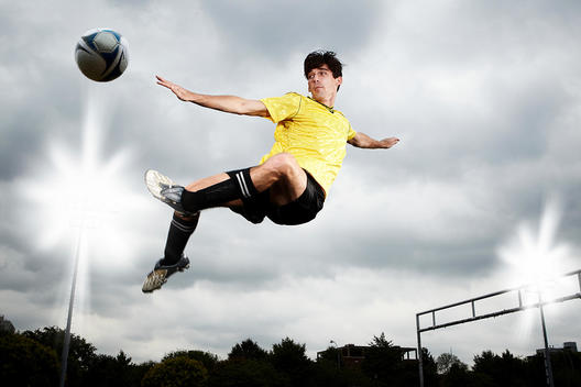 Soccer Player Leaping To Kick Ball