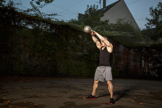 Muscly young man training with dumbbell on sports field