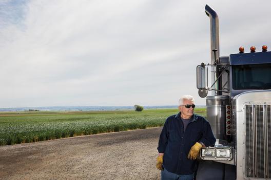 Caucasian trucker standing by truck