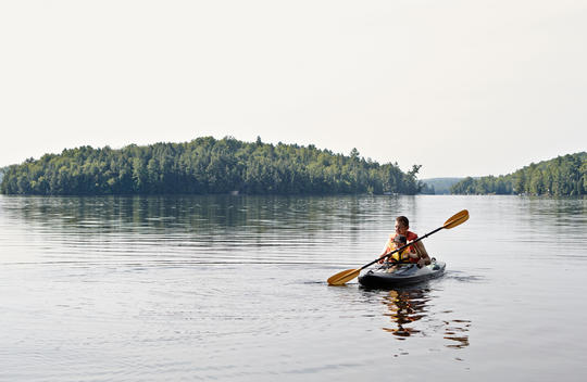 Father and son kayaking on lake, Ontario, Canada